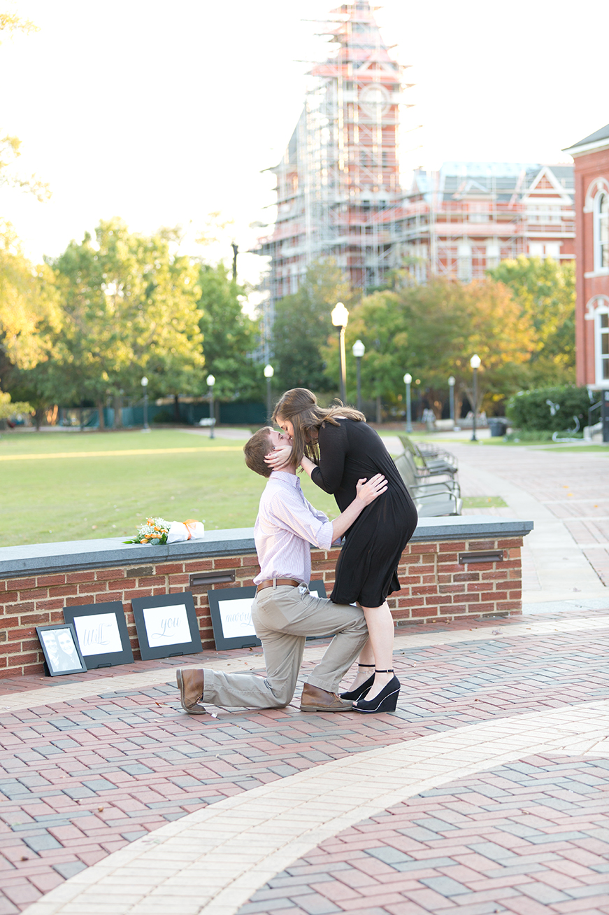 couple kisses after proposal at toomer's corner in auburn