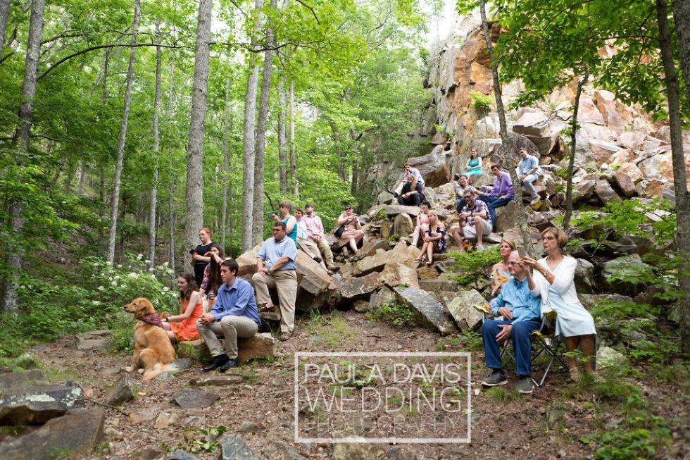wedding guests sitting on rocks