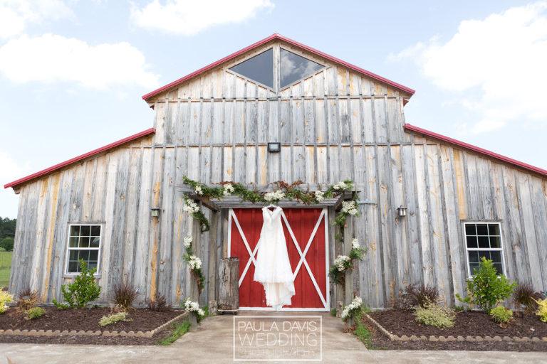 wedding dress hanging from barn