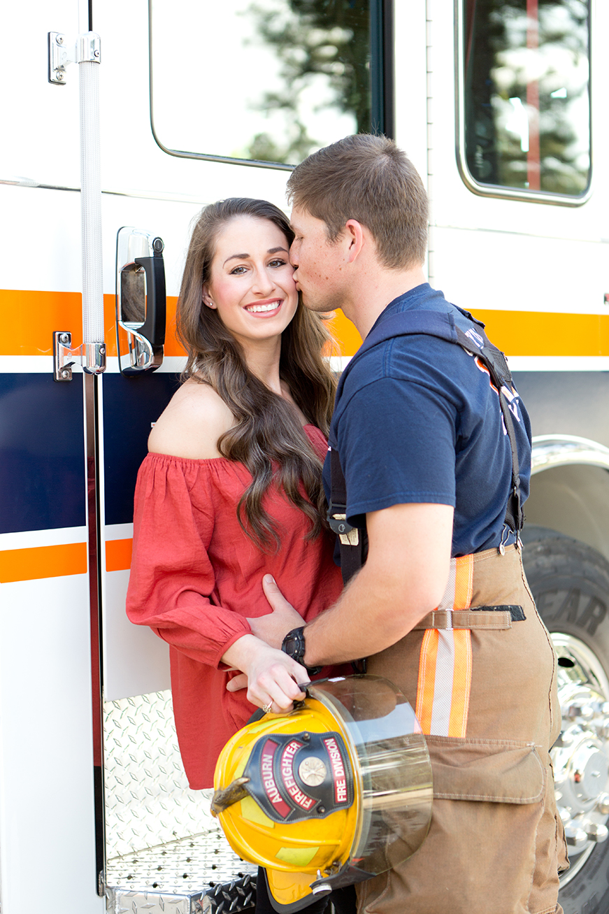 firefighter kissing woman on cheek next to auburn fire truck
