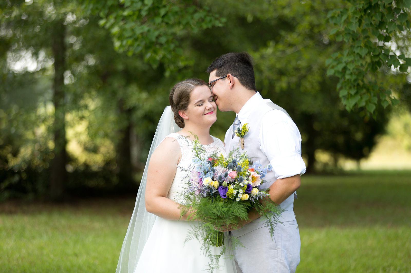 groom kisses bride on the head outside a home in shorter alabama