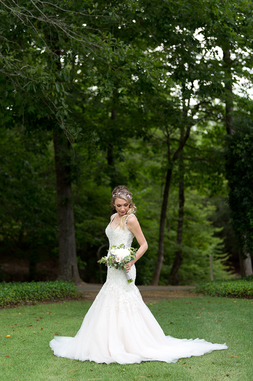 bride looks down at her bouquet behind moore's mill golf club