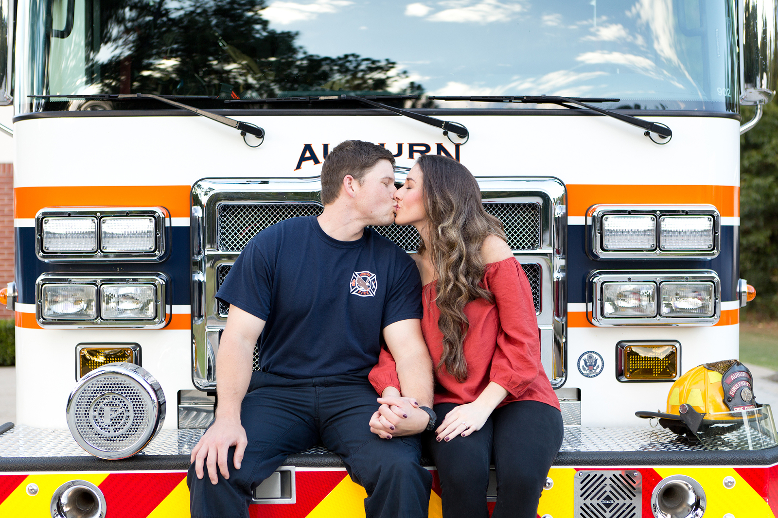 couple kissing while sitting on the front of an auburn fire truck