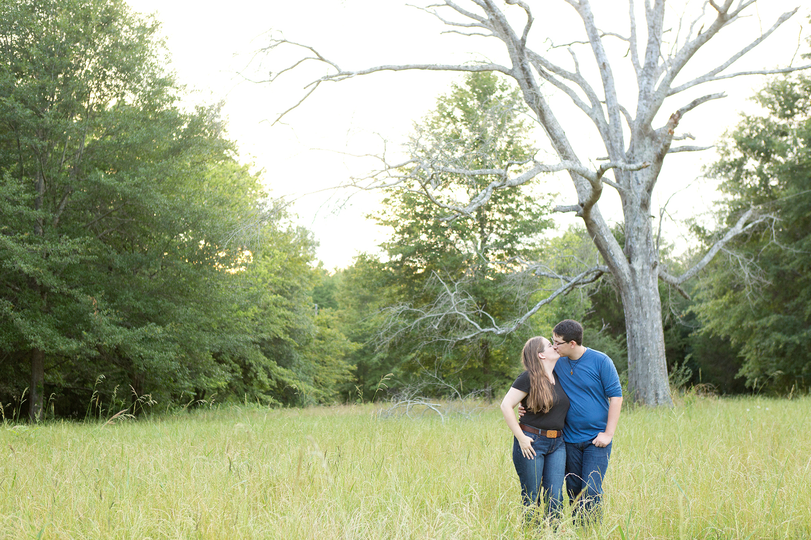 couple stands together in a field with a big tree on private land near shorter alabama