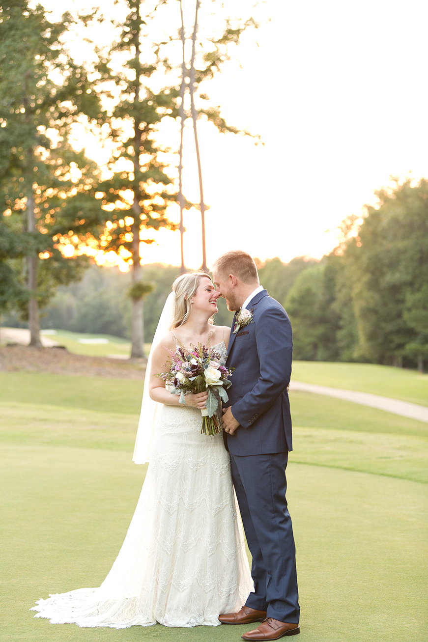 bride and groom smile close on the golf course at the auburn university club