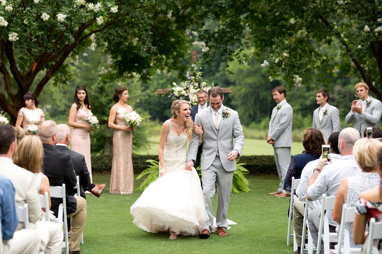 bride and groom laugh as they walk down the aisle after their wedding at moore's mill golf club