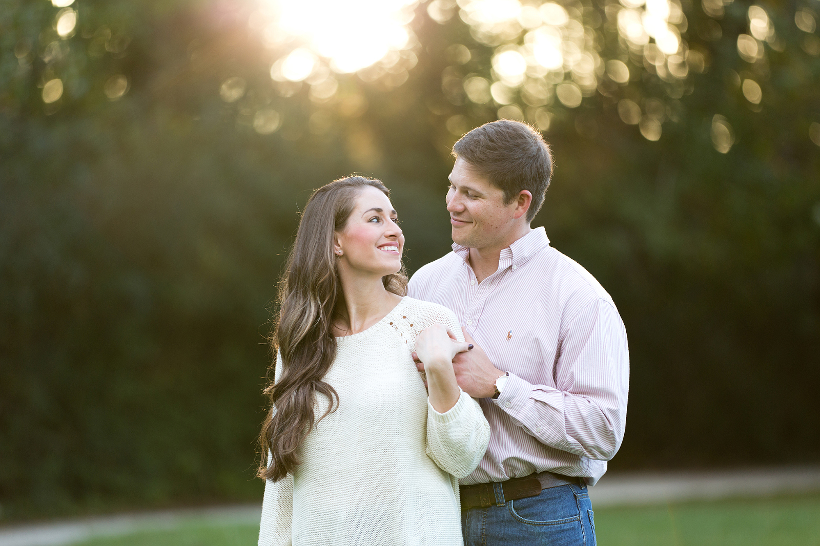 couple smile together in a field during an engagement session