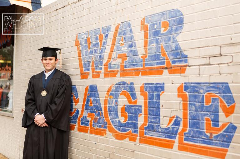 auburn graduate standing near the war eagle wall