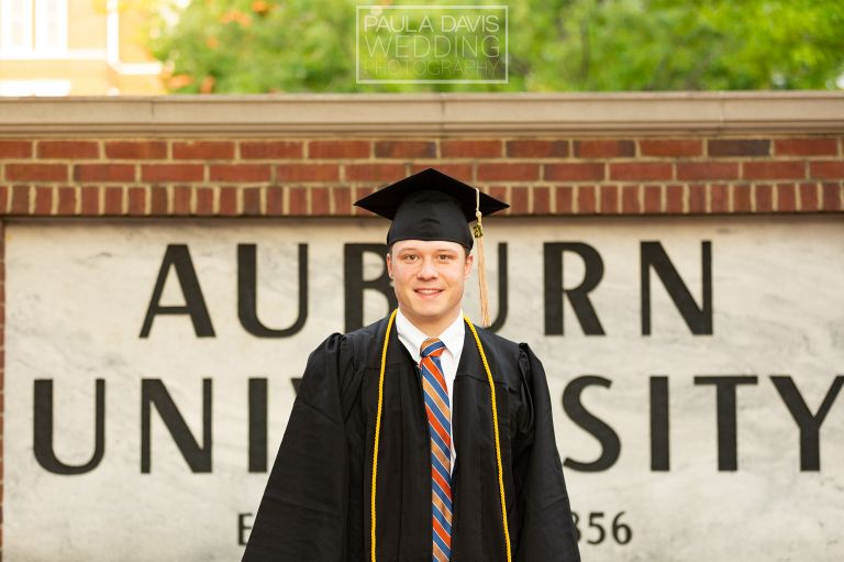 student in cap and gown by auburn university sign