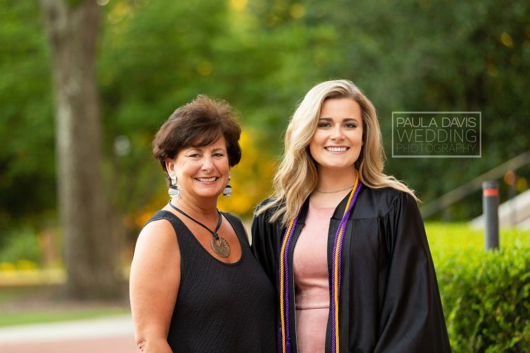 girl in a graduation gown next to her mom by samford hall