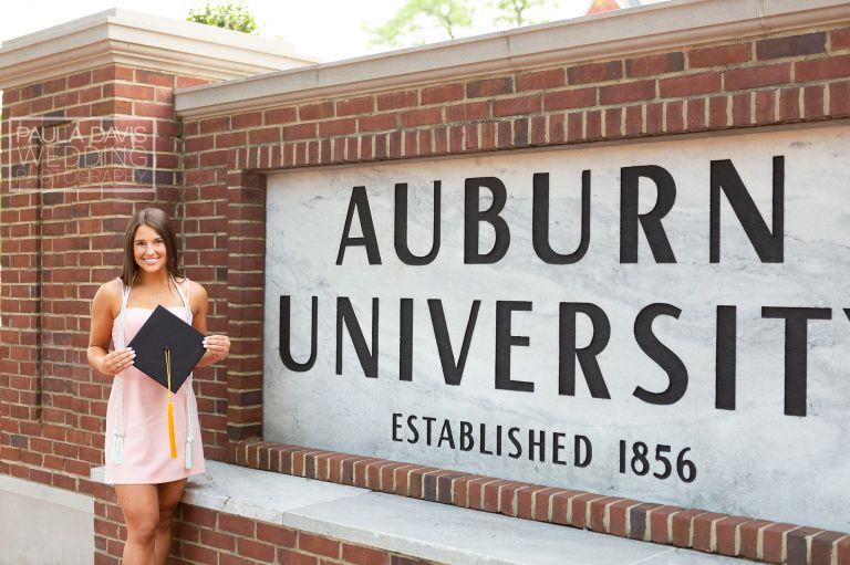 girl standing next to auburn university sign holding her graduation cap