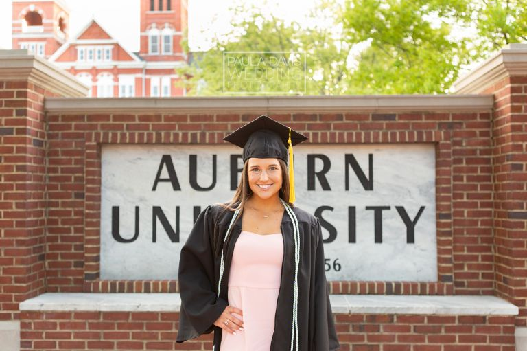 girl in pink dress in front of auburn university sign wearing cap and gown