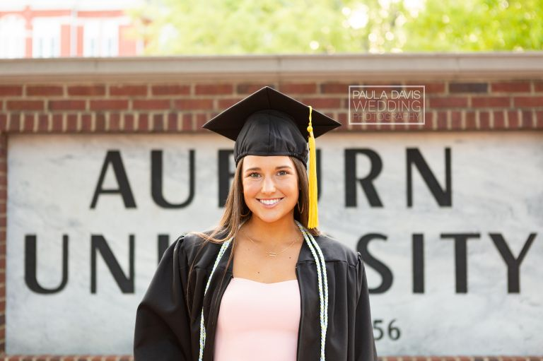 girl standing in front of auburn university sign in graduation cap and gown