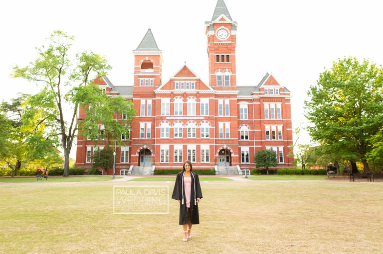 girl in graduation gown in front of samford hall